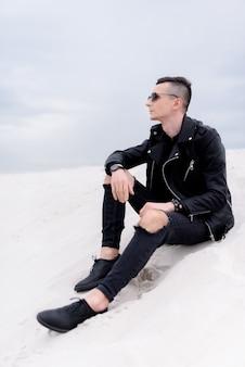 Zijaanzicht van knappe man zittend op de zandheuvel