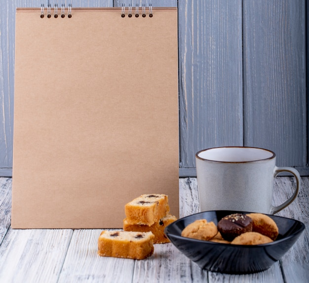 Zijaanzicht van koekjes op een kom en een kop thee op plattelander