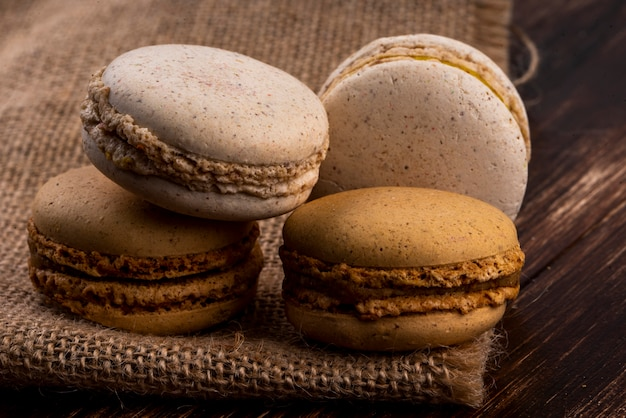 Zijaanzicht van koekjessandwiches op jute en houten achtergrond