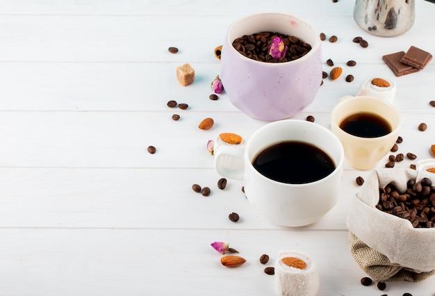 Zijaanzicht van koffiebonen in een kom en kopjes koffie op witte achtergrond met kopie ruimte