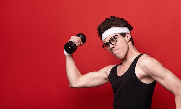 Zijaanzicht van komische magere jonge man in sportkleding en brillen grappige ernstig gezicht maken terwijl het doen van biceps-oefening met halter