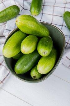 Zijaanzicht van komkommers in kom met andere op geruite doek en houten tafel