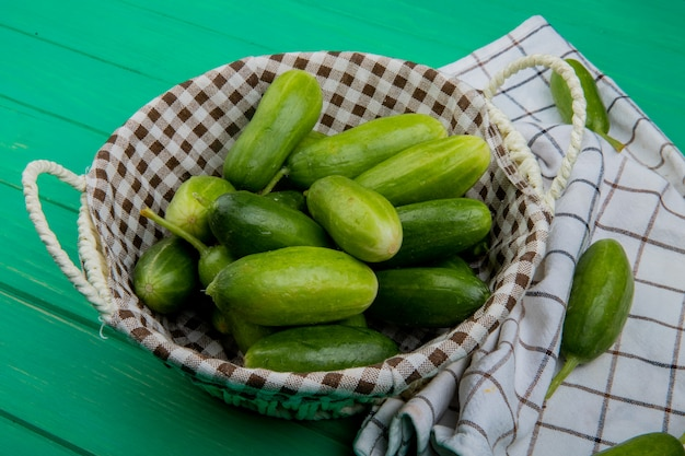 Zijaanzicht van komkommers in mand met andere op doek en groene tafel