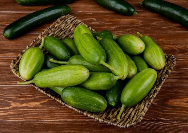 Zijaanzicht van komkommers in mandplaat met andere op houten oppervlakte