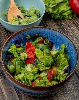 Zijaanzicht van kommen van groentesalades met de houten tomaat van de lepelsla op houten lijst