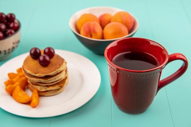 Zijaanzicht van kopje koffie met plaat van pannenkoeken en abrikozenplakken met kersen en kommen van kers en abrikoos op blauwe achtergrond