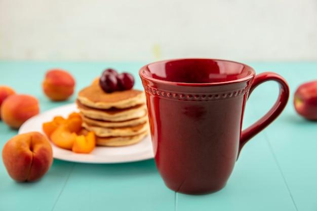 Zijaanzicht van kopje koffie met plaat van pannenkoeken en abrikozenplakken met kersen op blauwe ondergrond en witte achtergrond