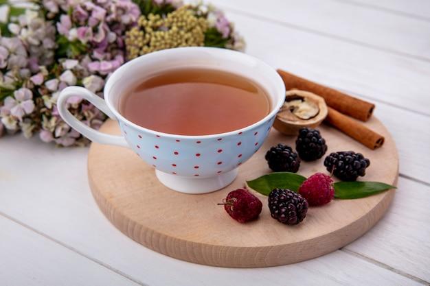 Zijaanzicht van kopje thee met kaneel noten frambozen en bramen op een snijplank met bloemen op een wit oppervlak