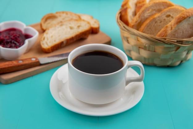 Zijaanzicht van kopje thee met sneetjes brood en frambozenjam op snijplank op blauwe achtergrond