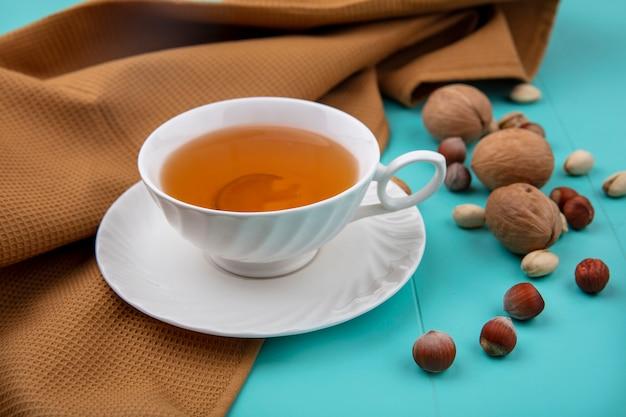 Zijaanzicht van kopje thee met walnoten, hazelnoten met pistachenoten met een bruine handdoek op een turkoois oppervlak