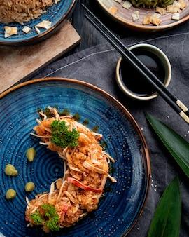 Zijaanzicht van krabsalade met groenten en wasabi op een plaat en sojasaus op zwarte