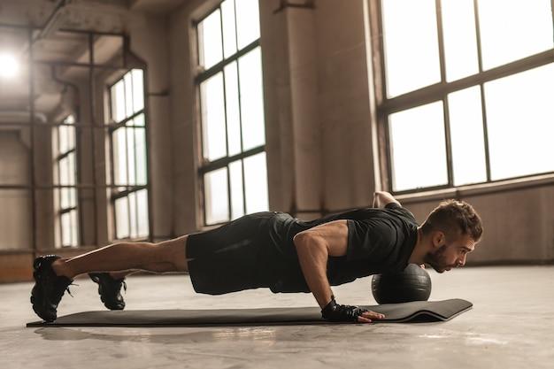 Zijaanzicht van krachtige mannelijke atleet doet push-ups met bal op mat tijdens het trainen in ruime sportschool