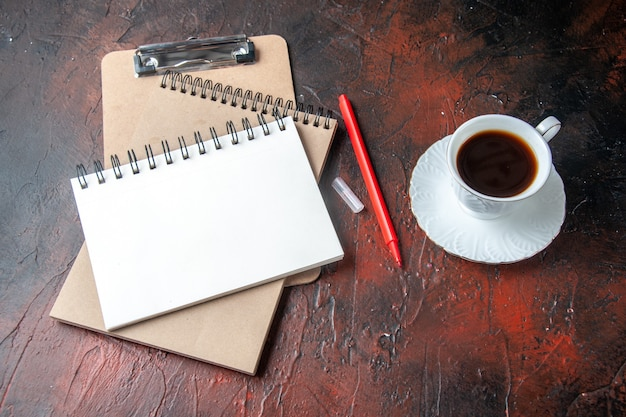 Zijaanzicht van kraftpapier-spiraalnotitieboekjes met pen en een kopje thee op donkere achtergrond