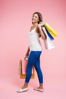 Zijaanzicht van lachende jonge vrouw lopen met kleurrijke boodschappentassen
