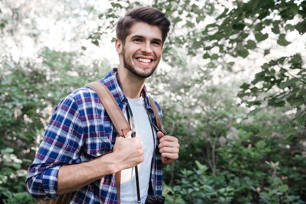 Zijaanzicht van lachende man met rugzak in bos
