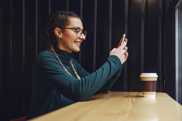 Zijaanzicht van lachende meisje zit in coffeeshop, met behulp van slimme telefoon om te chatten met vriendje.