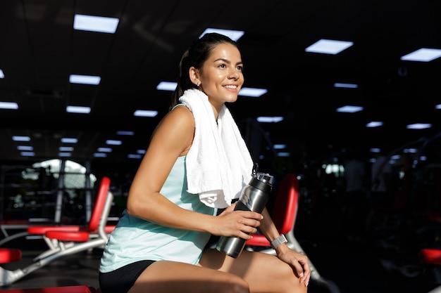 Zijaanzicht van lachende sportvrouw ontspannen en wegkijken zittend op een bankje in de sportschool