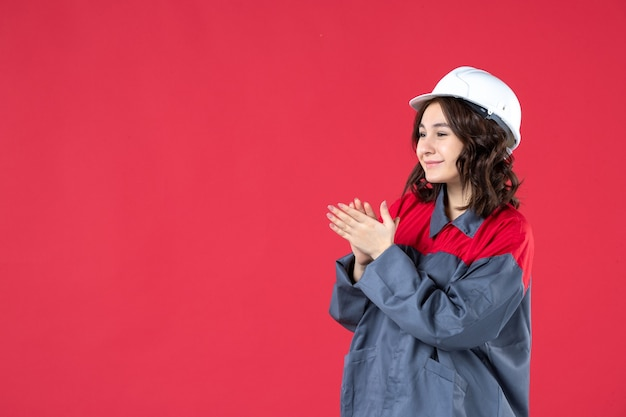 Zijaanzicht van lachende vrouwelijke bouwer in uniform met harde hoed en iemand applaudisseren op geïsoleerde rode achtergrond