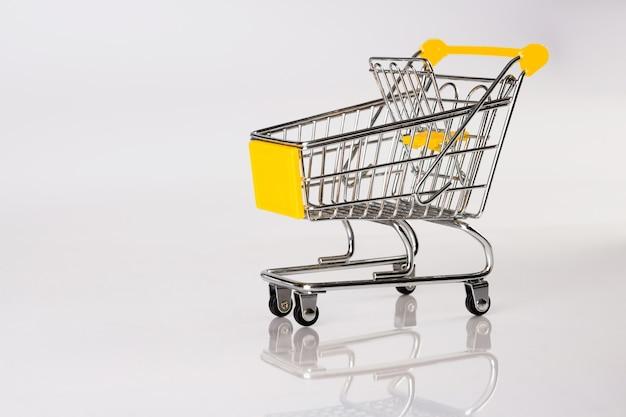 Zijaanzicht van lege mini-trolley met reflectie op wit oppervlak