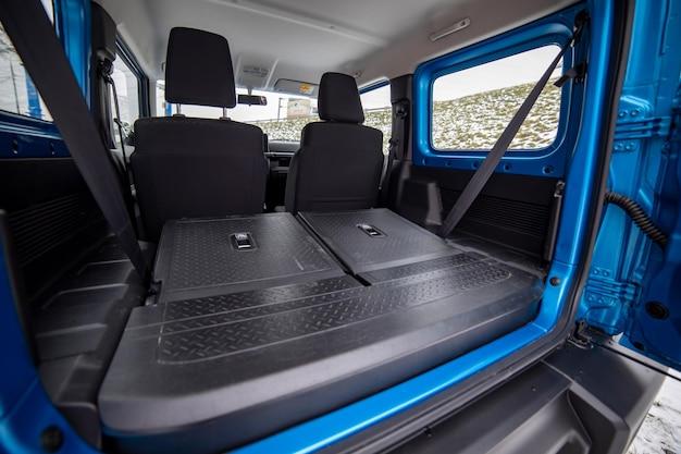 Zijaanzicht van lege open kofferbak met stoelen opgevouwen in platte flor van suv crossover open deur