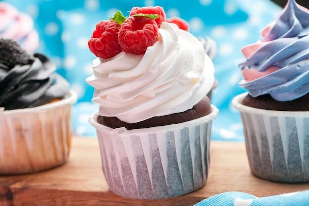 Zijaanzicht van lekkere cupcakes met geassorteerde smaak. geschoten op de tafel