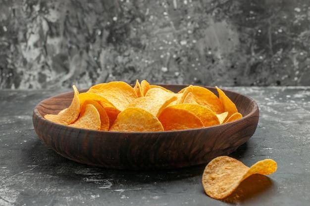 Zijaanzicht van lekkere zelfgemaakte aardappelchips op een bruine plaat en op grijze tafel gelegd