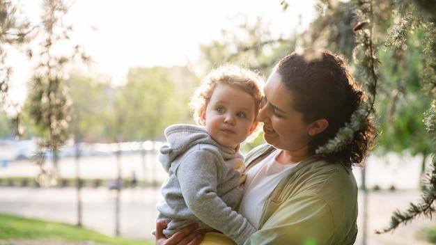 Zijaanzicht van lgbt-moeder buiten in het park met haar kind
