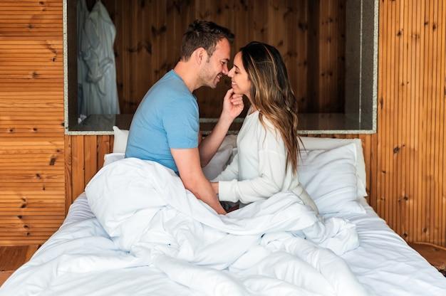 Zijaanzicht van liefdevolle man en vrouw kussen zittend samen in gezellig bed na het ontwaken in de ochtend