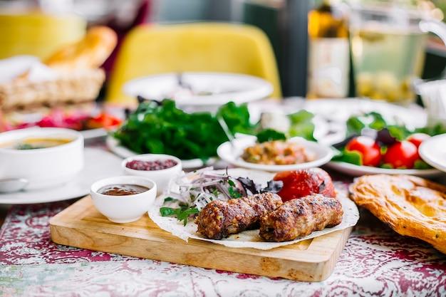 Zijaanzicht van lula kebab op lavash met de geroosterde ui van kruiden verse tomaten en spicies op een houten raad