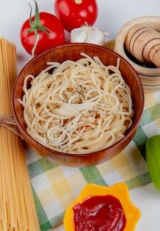 Zijaanzicht van macaroni pasta in kom met tomaten zwarte peper ketchup knoflook peper en vermicelli op geruite doek