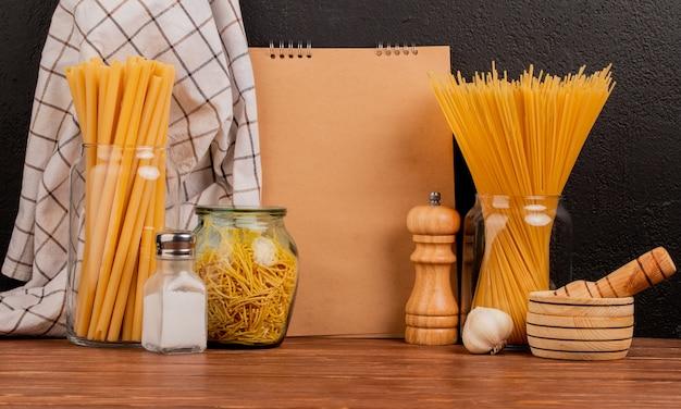 Zijaanzicht van macaronis als bucatini en spaghetti in potten met zout knoflook knoflook crusher doek en notitieblok op houten oppervlak en zwarte achtergrond met kopie ruimte