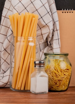 Zijaanzicht van macaronis als bucatini en spaghetti met zout en geruite doek en notitieblok op houten oppervlak