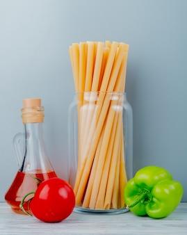 Zijaanzicht van macaronis als bucatini met tomatenpeper en boter op houten oppervlakte en blauwe muur
