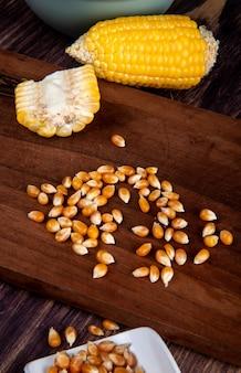 Zijaanzicht van maïszaden en gesneden maïs op snijplank en houten tafel