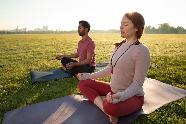 Zijaanzicht van man en vrouw die buiten mediteren op yogamatten