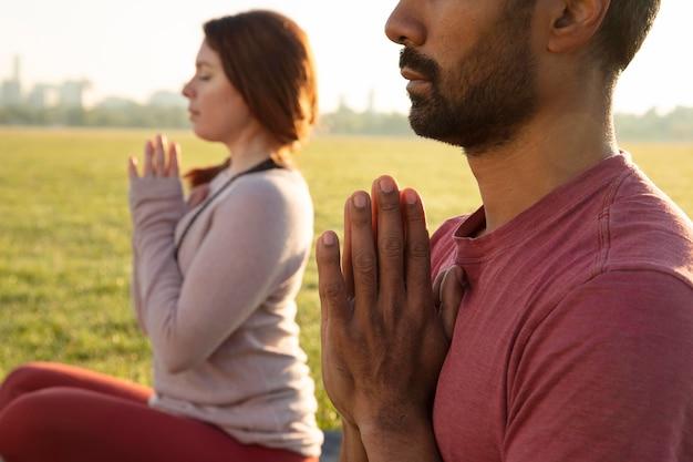 Zijaanzicht van man en vrouw die buiten mediteren