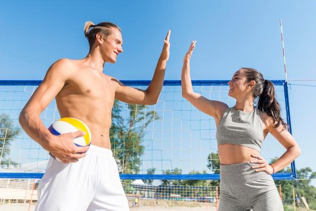 Zijaanzicht van man en vrouw die elkaar high-fiving tijdens het spelen van volleybal