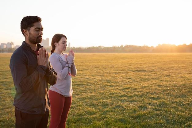 Zijaanzicht van man en vrouw die samen buiten yoga doen