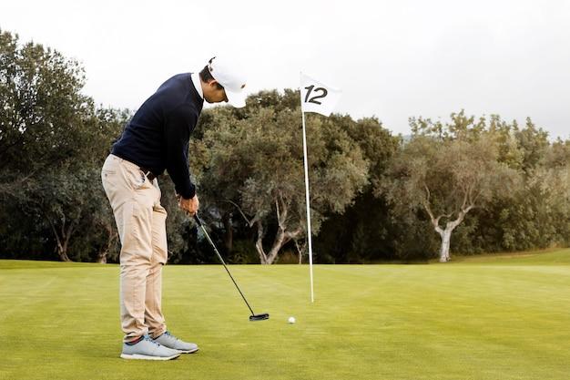 Zijaanzicht van man golfen