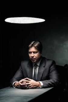 Zijaanzicht van man in pak zittend in donkere kamer alleen verlicht door licht van een lamp