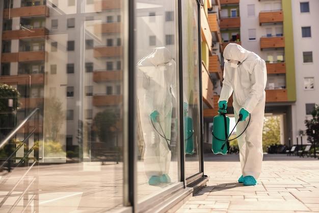 Zijaanzicht van man in steriel beschermend uniform met rubberen handschoenen die sproeier met desinfectiemiddel vasthoudt en buitenshuis sproeit om verspreiding van het coronavirus te voorkomen