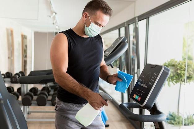Zijaanzicht van man met medisch masker fitnessapparatuur desinfecteren