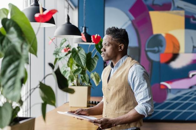 Zijaanzicht van man met papieren op de werkplek