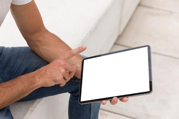 Zijaanzicht van man met tablet buitenshuis