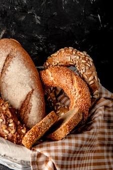 Zijaanzicht van mand van brood op zwarte oppervlakte