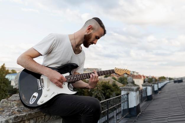 Zijaanzicht van mannelijke artiest op dak elektrische gitaar spelen