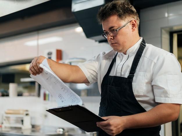 Zijaanzicht van mannelijke chef-kok die klembord controleert