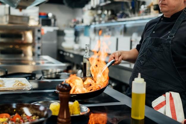 Zijaanzicht van mannelijke chef-kok flambeing schotel
