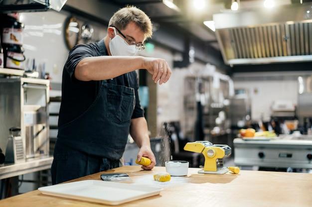 Zijaanzicht van mannelijke chef-kok met de deegwaren van het maskerkruiden