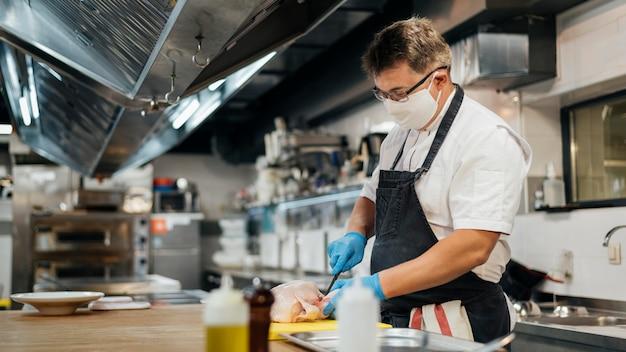 Zijaanzicht van mannelijke chef-kok met masker scherpe kip